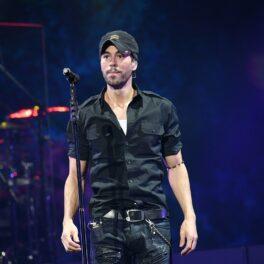 Enrique Iglesias într-o cămașă neagră și o pereche de blugi negri în timp ce se află pe o scenă