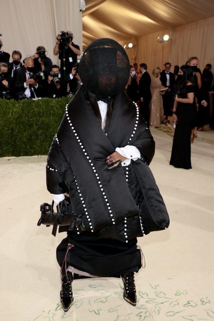 Erykah Badu într-o ținută neagră cu fața acoperită în timp ce pozează la Met Gala 2021