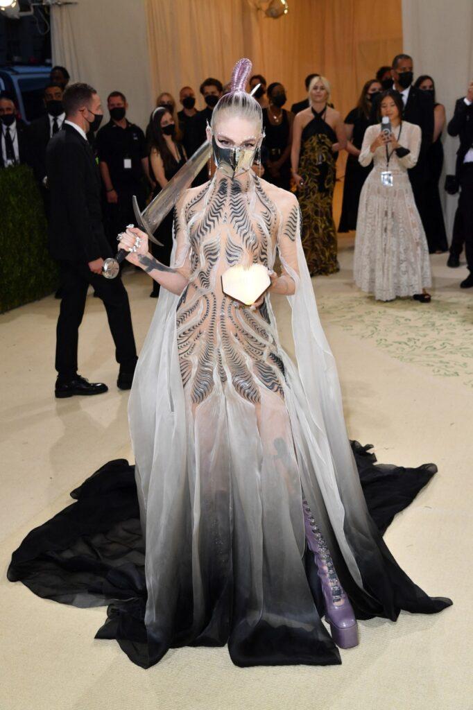 Grimes într-o rochie semitransparentă albă cu desene negre în timp ce ține în mână o sabie și alege una din ținutele creative de la Met Gala 2021