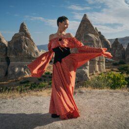 Irina Fodor, prezentatoarea emisiunii Asia Express: Drumul Împăraților într-o rochie lungă portocalie pe un deal din Turcia