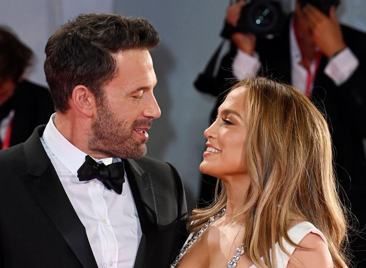 Ben Affclek la costum negru cu papion în timp ce o privește în ochi pe Jennifer Lopez care poartă o rochie albă
