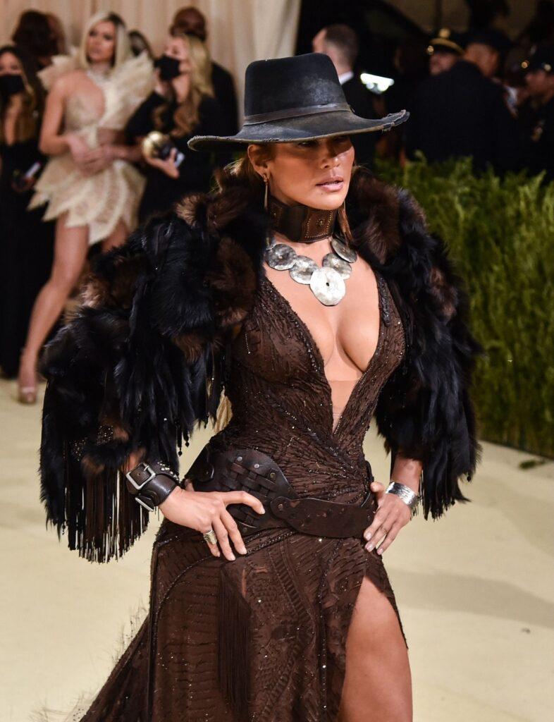 Jennifer Lopez într-o rochie mulată maro, peste care are o mantie cu pene și o pălărie de piele la Met Gala 2021
