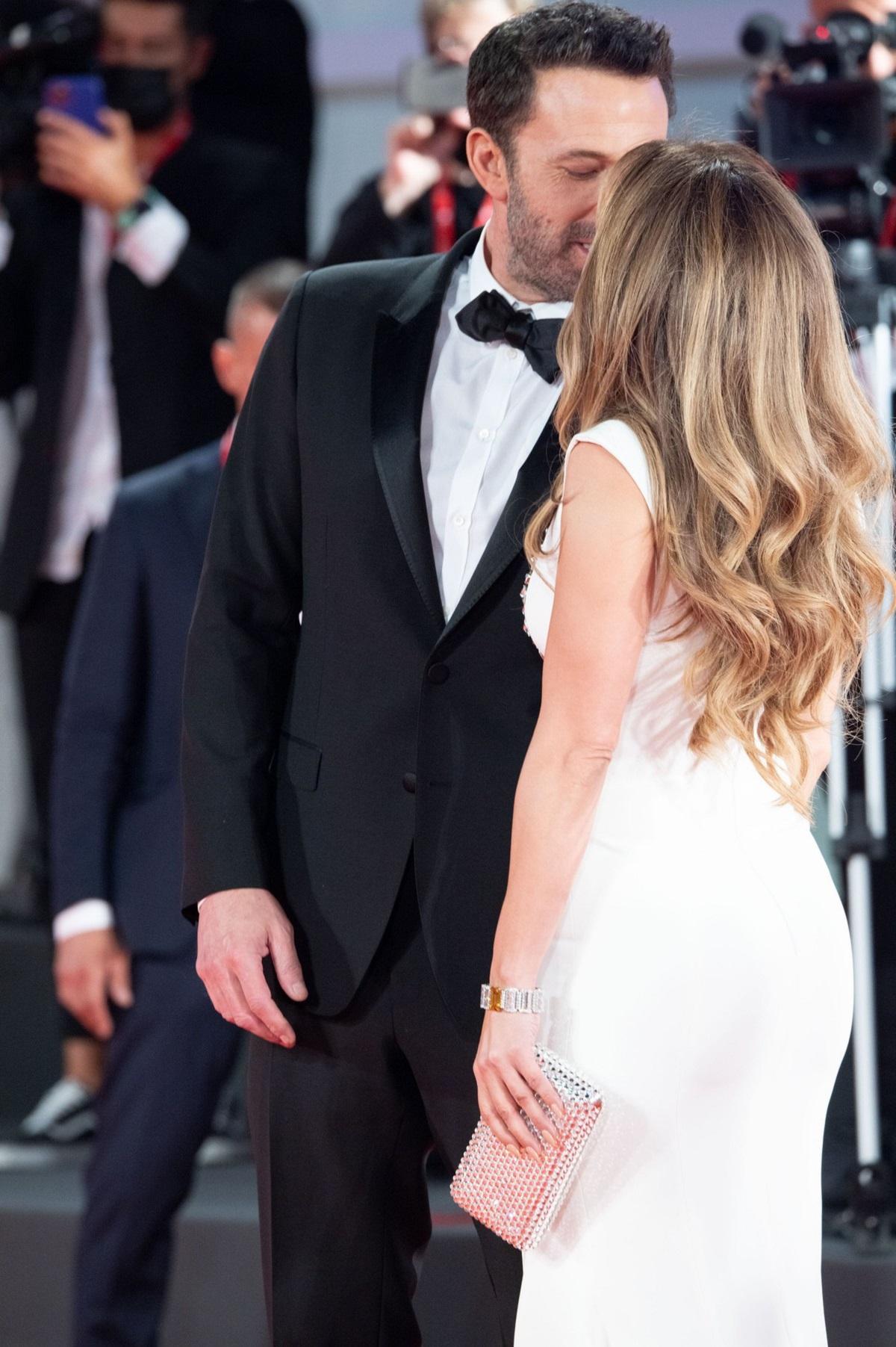 Ben Affleck în smoching negru în timp ce o sărută pe Jennifer Lopez pe covorul roșu