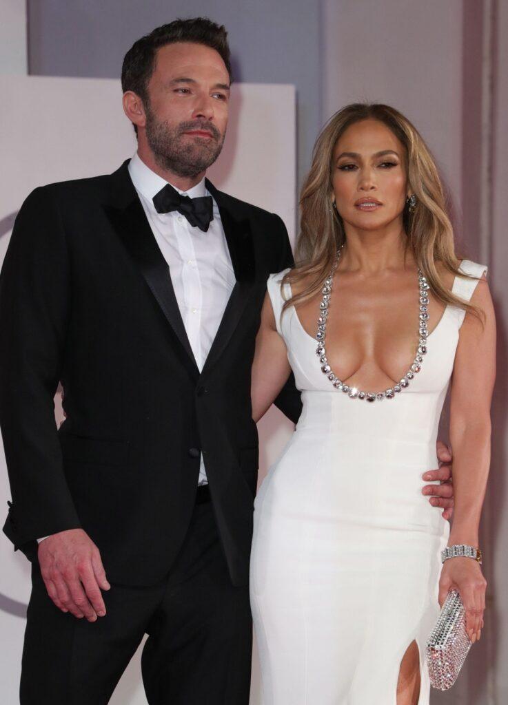 Jennifer Lopez într-o rochie albă cu decolteu alături de Ben Affleck la costum negru pe covorul roșu la Fesivalul de Film de la Veneția