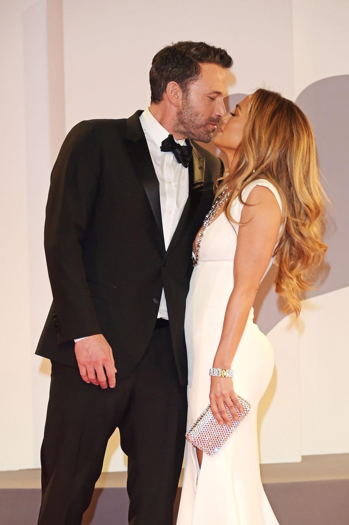 Ben Affleck la costum negru în timp ce o sărută pe Jennifer Lopez care poartă o rochie albă lungă