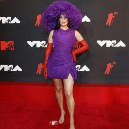 Kacey Musgraves într-o rochie mov cu o pălărie cu pene și o pereche de mănuși din latex roșii la MTV VMA 2021
