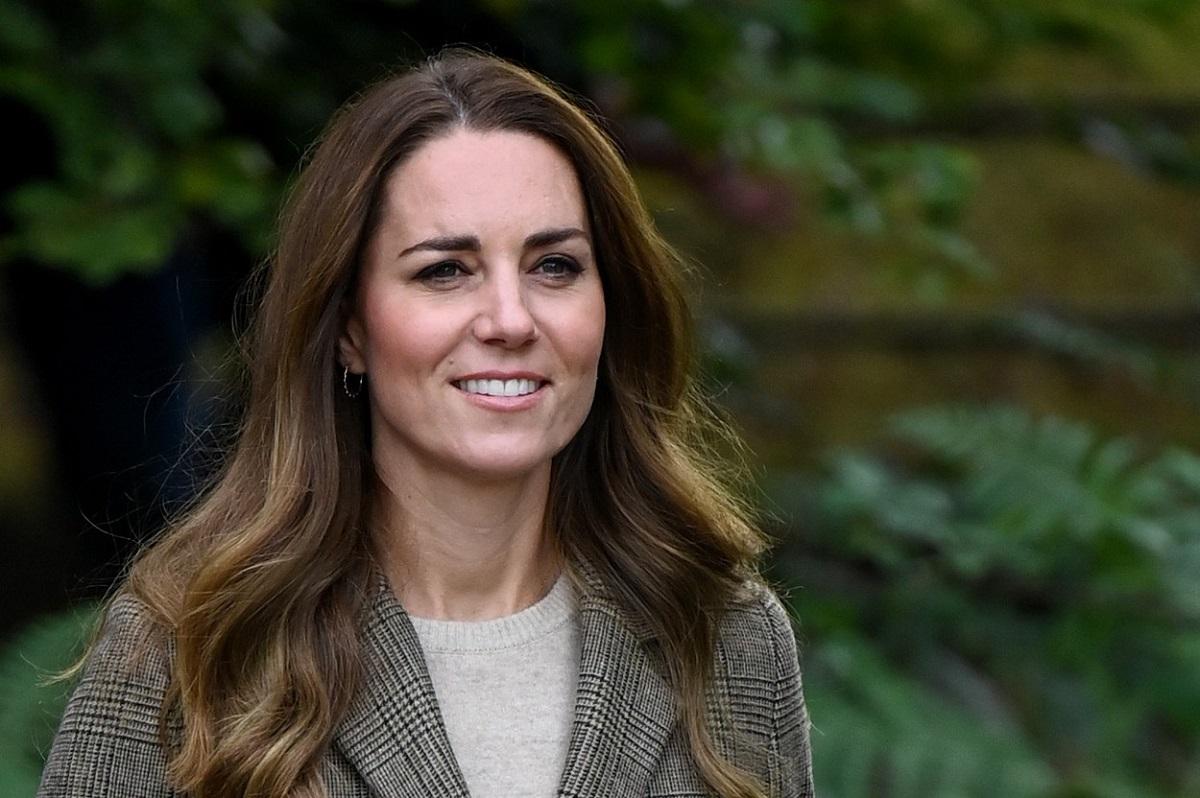 Kate Middleton zâmbind în timp ce poartă o bluză gri și un sacou în carouri