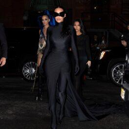 Kim Kardashian îmbrăcată într-un costum negru mulat cu trenă în timp ce merge la petrecerea după Met Gala 2021