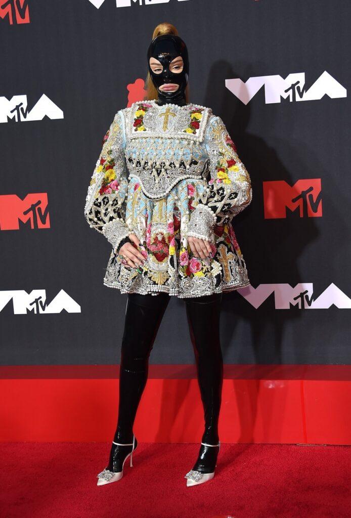 Kim Petras purtând o rochie scurtă cu inspirații religioase și o mască din latex negru pe covorul roșu la MTV VMA 2021