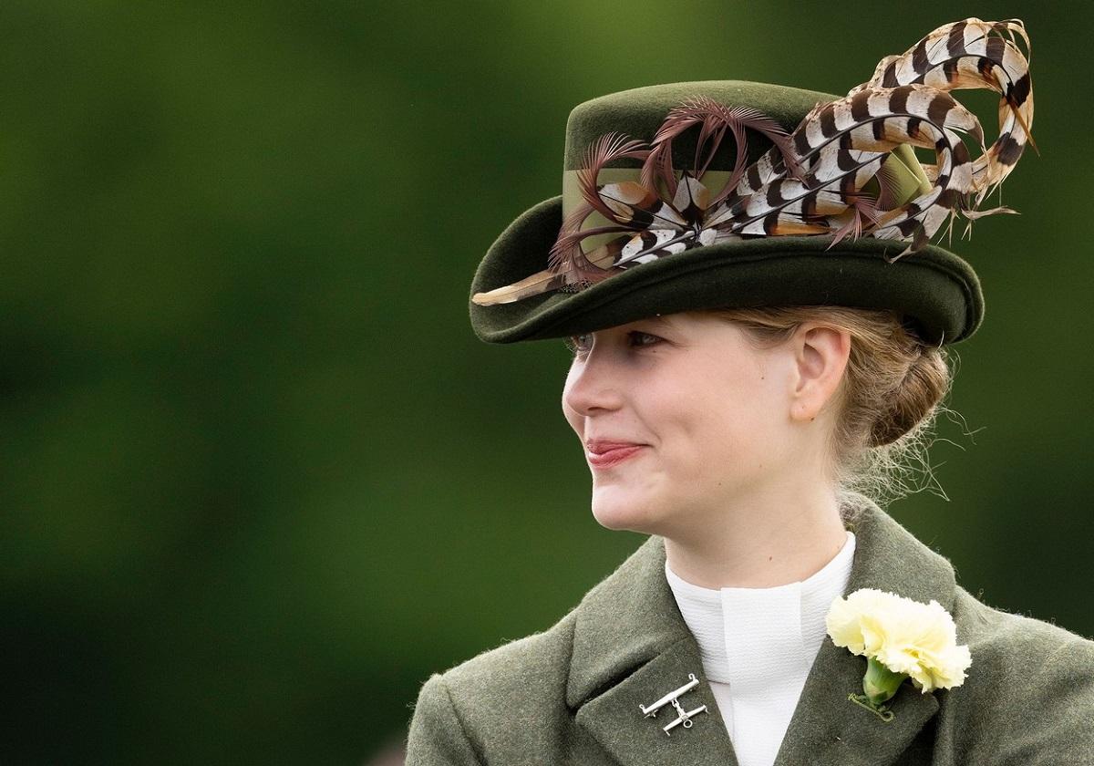 Portret al lui Lady Louise Windsor care poartă o pălărie verde decorată cu pene și un sacou verde în timp ce se plimbă cu trăsura