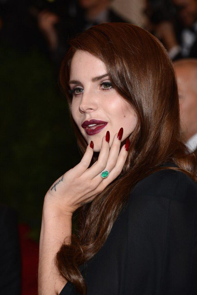 Câtăreața Lana Del Rey cu ruj roșu în timp ce își aranjează părul, a renunțat la rețelele sociale