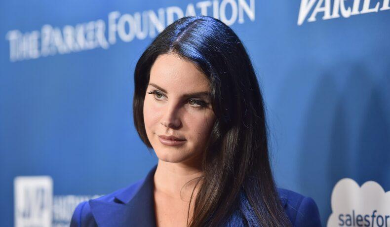 Lana Del Rey cu părul desprins în timp ce paortă un sacou și pozează pe covorul roșu