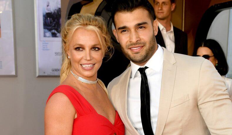 Britney Spears într-o rochie roșie alături de logodnicul său Sam Asghari care poartă un costum crem și o cravată neagră