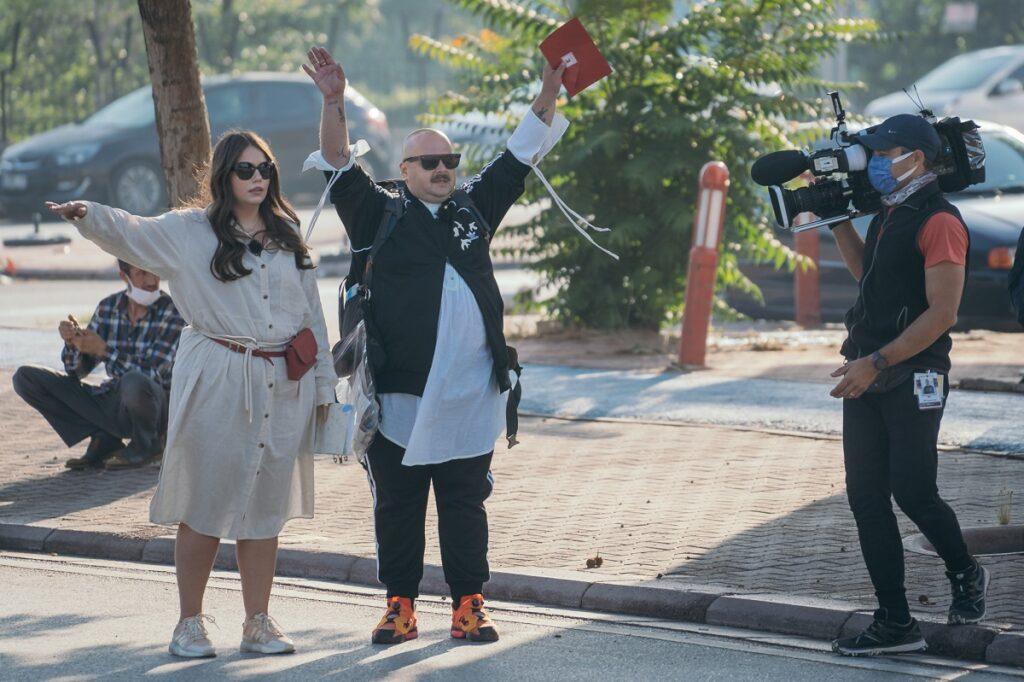 Lorelei Bratu într-o rochie crem în timp ce ține o mână ridicată alături de Mihai Dan Zarug la competiția Asia Express: Drumul Împăraților
