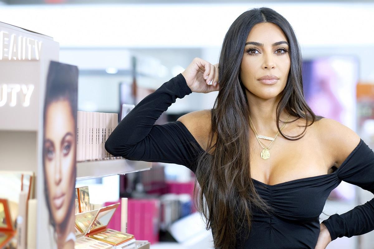Machiajul lui Kim Kardashian natural care poartă o bluză neagră și stă sprijinită cu fața într-o mână la lansarea unui brand de machiaj