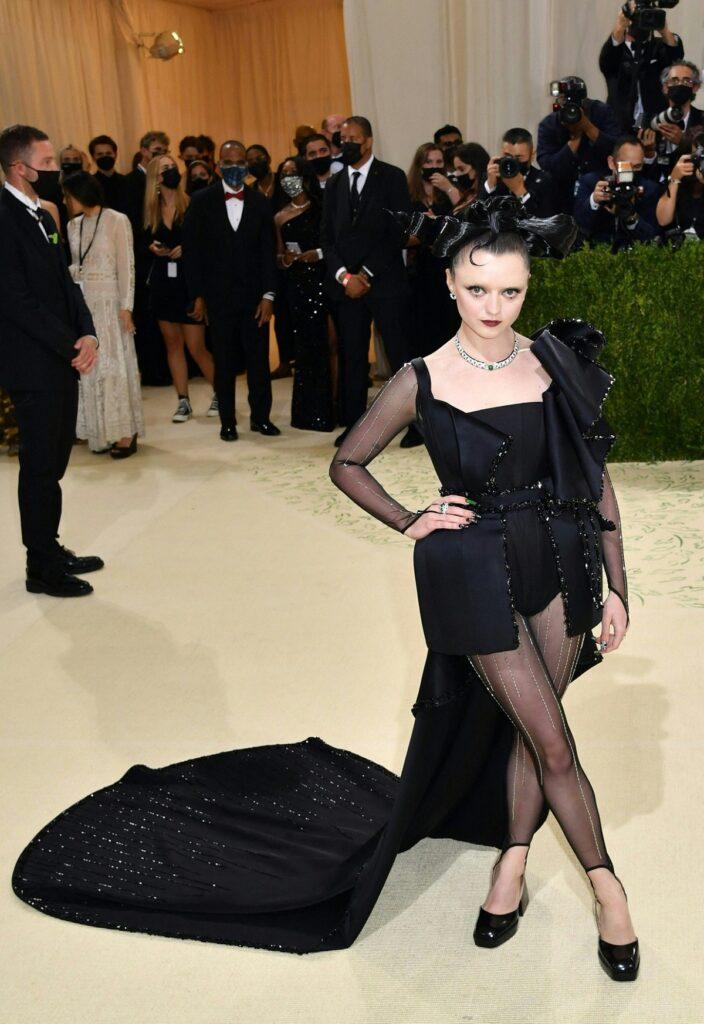 Maisie Williams într-o rochie neagră cu trenă și cu o mână în șold în timp ce pozează la Met Gala 2021