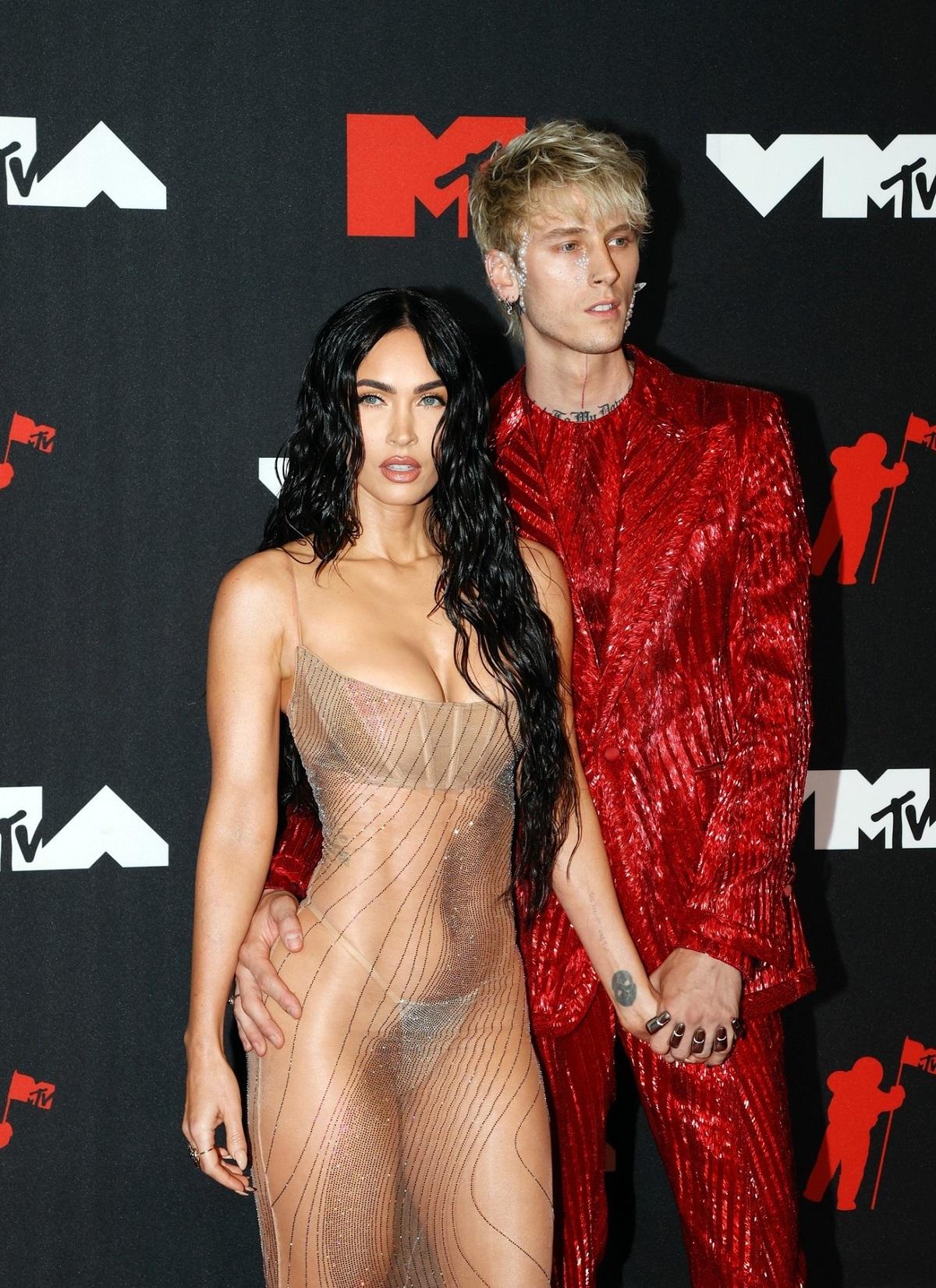 Megan Fox într-o rochie nude, transparentă, alături de iubitul său Machine Gun Kelly care a purtat un costum roșu cu paiete și au făcut parte din ținutele excentrice ale MTV VMA 2021