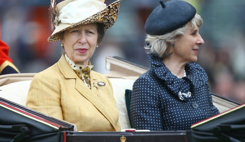 Prințesa Anne și Ducesa de Gloucester în trăsură. Anne proată o haină galbenă și o pălărie în aceeași nuanță. Ducesa de Gloucester poartă albastru