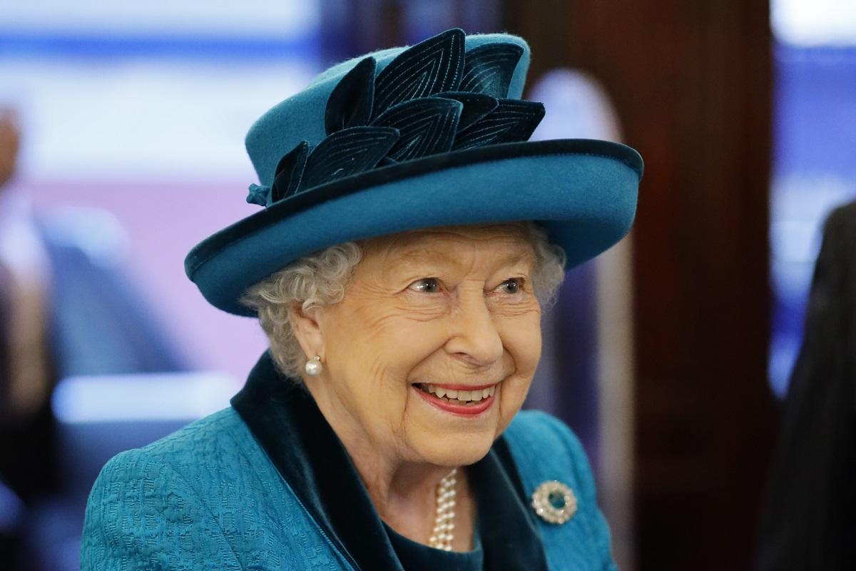 Portret al Reginei Elisabeta care poartă o pălărie albastră cu pene și un costum albastru în timp ce participă la o întâlnire oficială din anul 2019