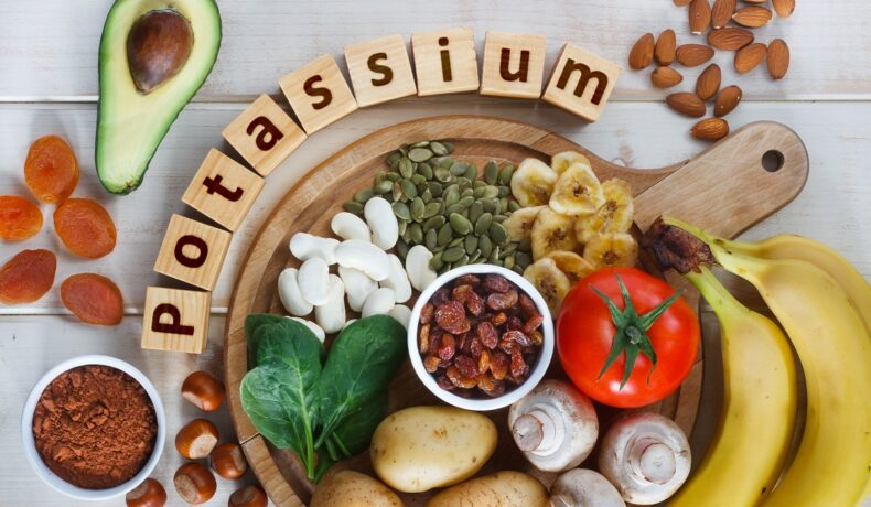 Un blat de bucătărie pe care se află alimente bogate în potasiu, printre care fasolea roșie, cartofii, roșii, ciuperci, avocado, banane și spanac, alături de care este scris cuvântul potasiu format din cubulețe cu litere