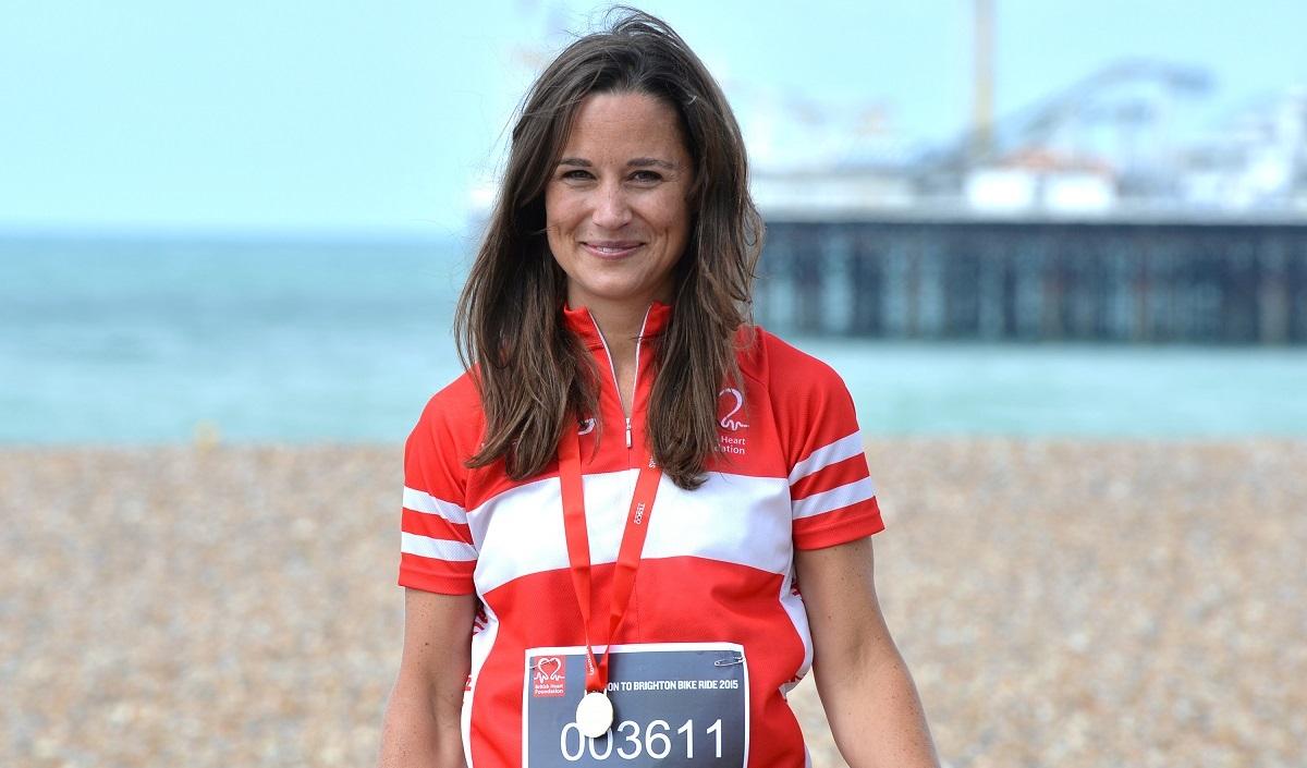 Pippa Middleton care poartă un tricou portocaliu cu dungi albe în timp ce stă pe o plajă și poartă o medalie la gât după ce a alergat la un maraton caritabil