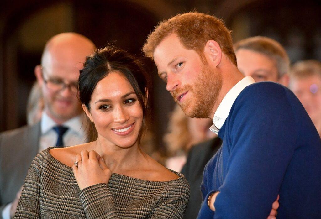 Meghan Markle într-o rochie gri în timp ce se află alături de Prințul Harry care poartă un sacou albastru