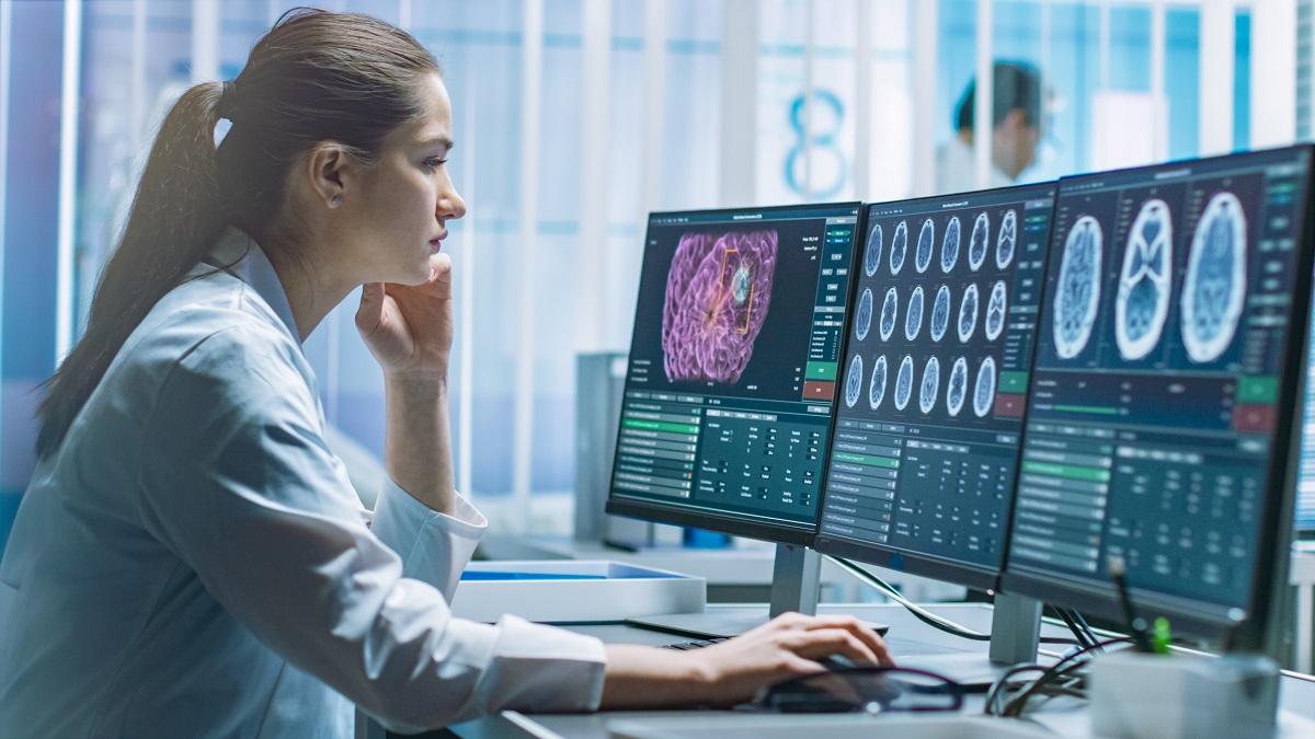 O femeie frumoasă îmbrăcată în halat alb de medic care stă în fața unui calculator și studiază mai multe imagini ale creierului pentru a-și da seama care sunt primele simptome ale demenței