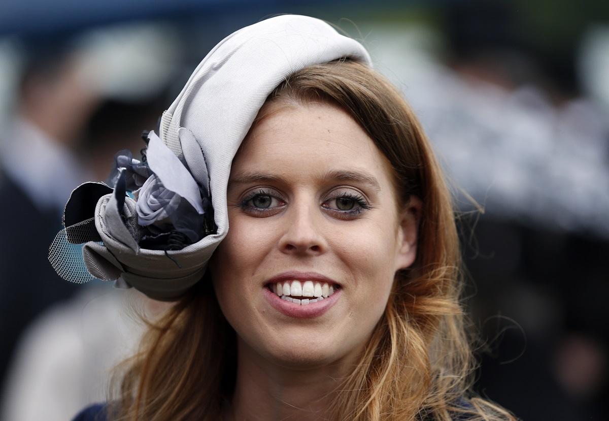 Prințesa Beatrice în timp ce zâmbește și poartă pe cap o pălărie gri