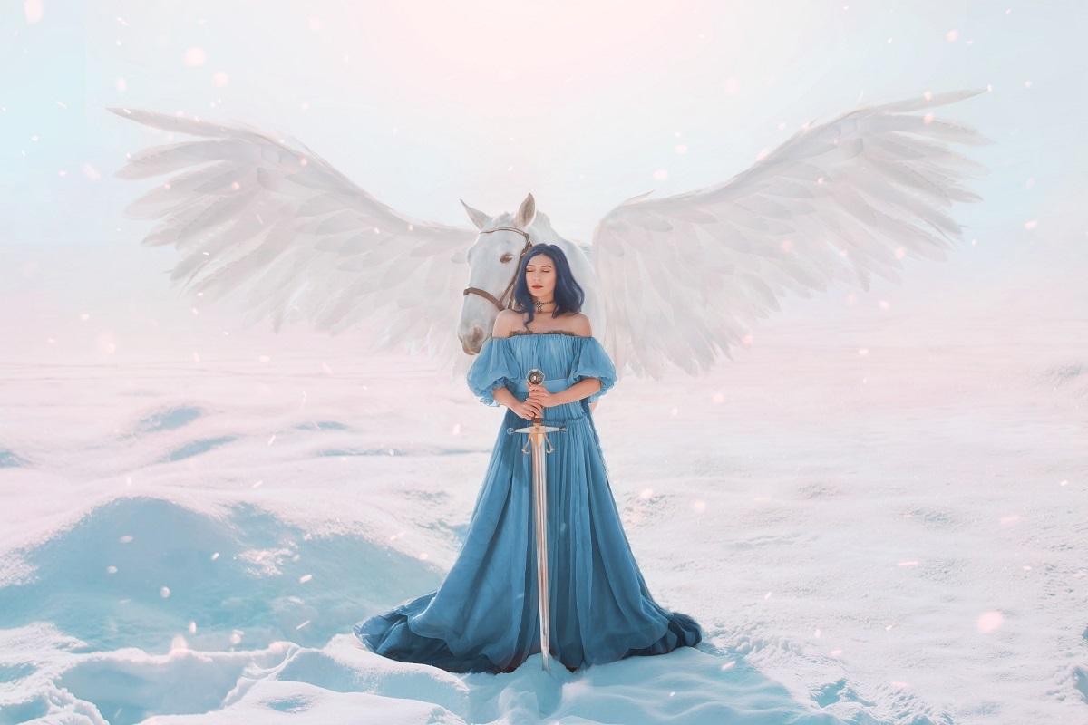 o femeie frumoasă care paortă o rochie albastră și se sprijină de o sabie în timp ce în spatele să se află un cal alb cu aripi penru a simboliza care sunt reacțiile zodiilor atunci când au o zi dificilă