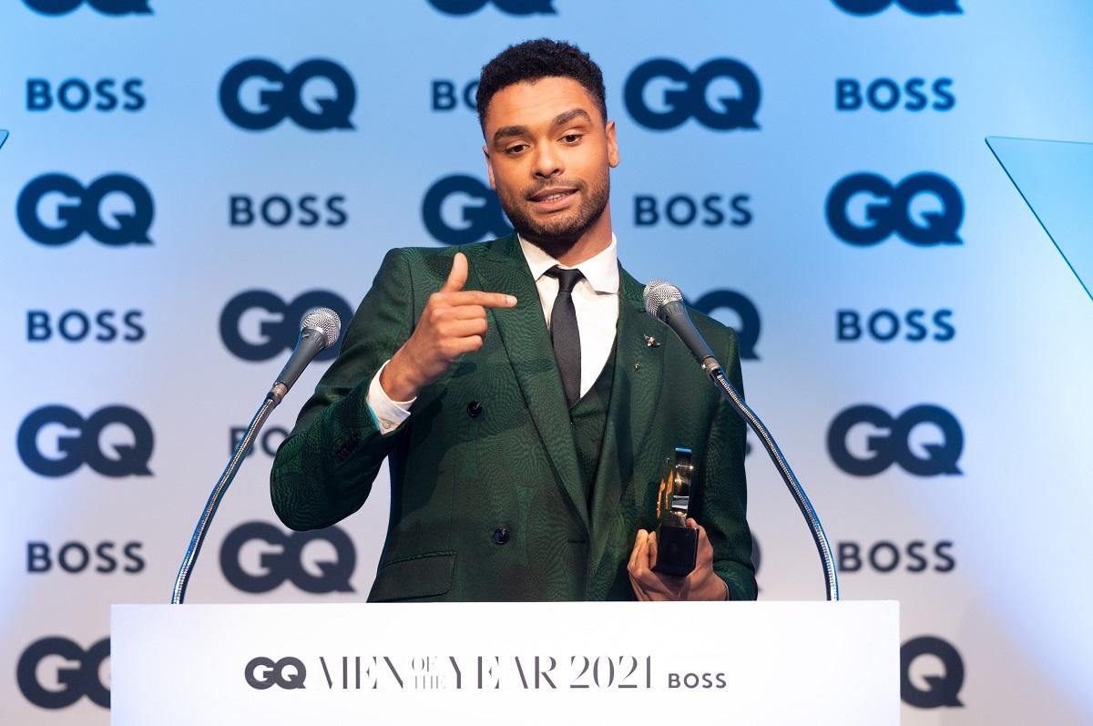 Regé-Jean Page purtând un costum verde smarald în timp ce ține un discurs după ce a primit un premiu pentru activitatea sa din ultimul an la festivitatea British GQ Men of the Year Awards 2021