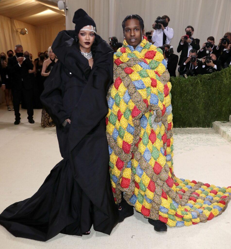 Rihanna și A$AP Rocky pe covorul roșu la Met Gala 2021 în timp ce poartă o rochie neagră, iar Asap poartă o pătură colorată