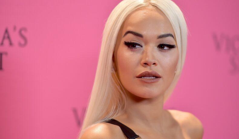 Portret al artistei Rita Ora cu părul lung blond dat pe spate în timp ce zâmbește la fotografi pentru evenimentul Victoria's Secret Fashion din 2018