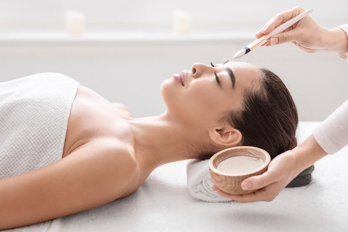 O femeie frumoasă care stă întinsă pe o masă de masaj și este acoperită cu un prosop alb în timp ce i se efectuează rutina de îngrijire coreeană în 10 pași.