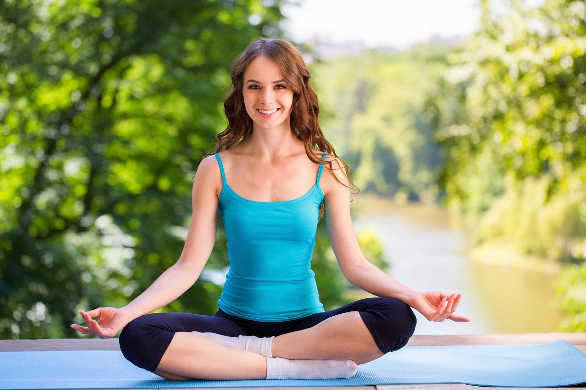 O femeie frumoasă care stă într-o poziție de meditație și poartă o bluză albastră și o pereche de colanți negri în timp ce practică o gândire pozitivă