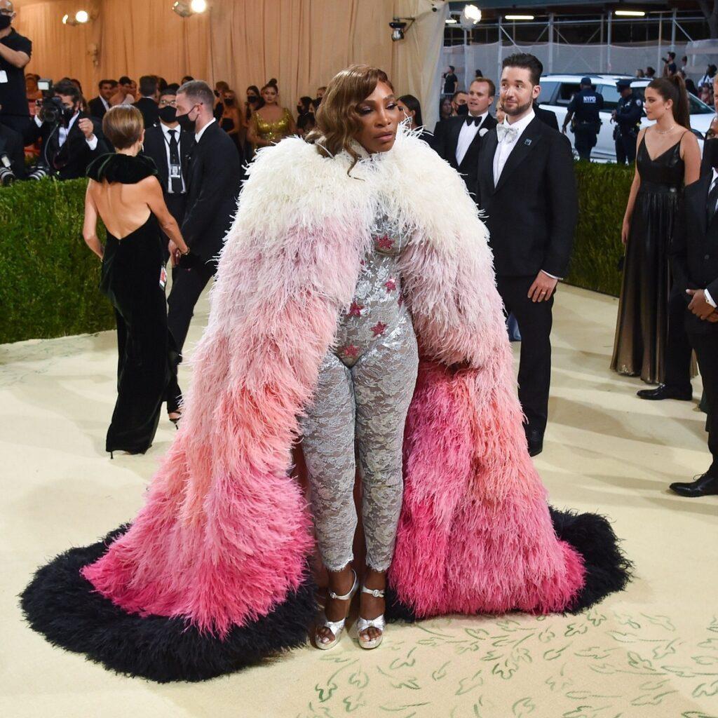 Serena Williams într-un costum din dantelă gri și o mantie cu pene alb cu roz la Met Gala 2021