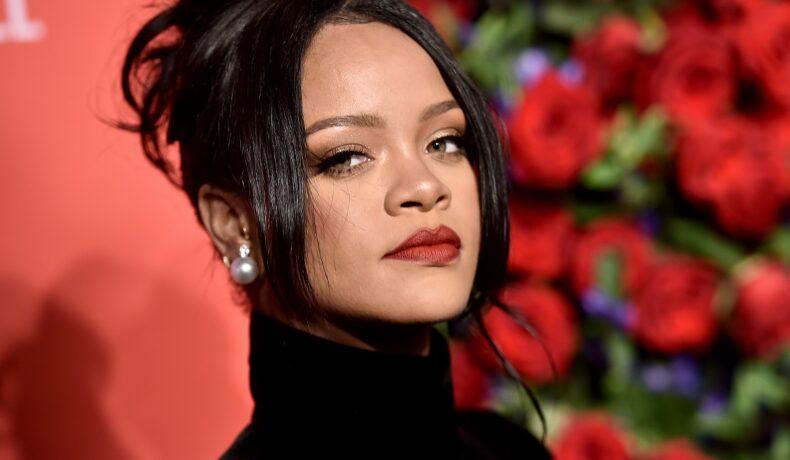 Rihanna cu părul prins în timp ce pozează în fața unui panou roșu