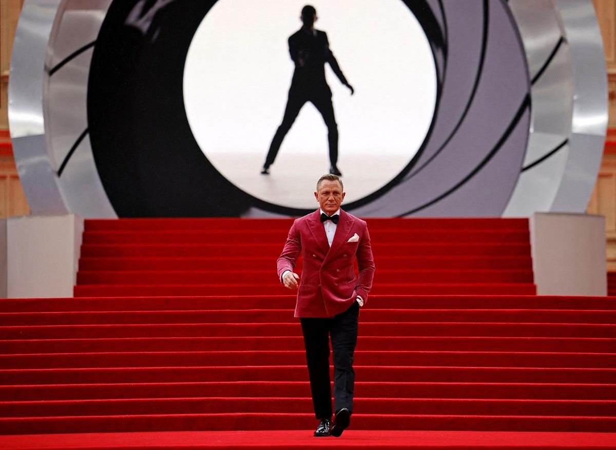 Daniel Craig într-un costum cu sacou roz în timp ce coboară scările acoperite de covorul roșu la premiera filmului James Bond No Time to Die