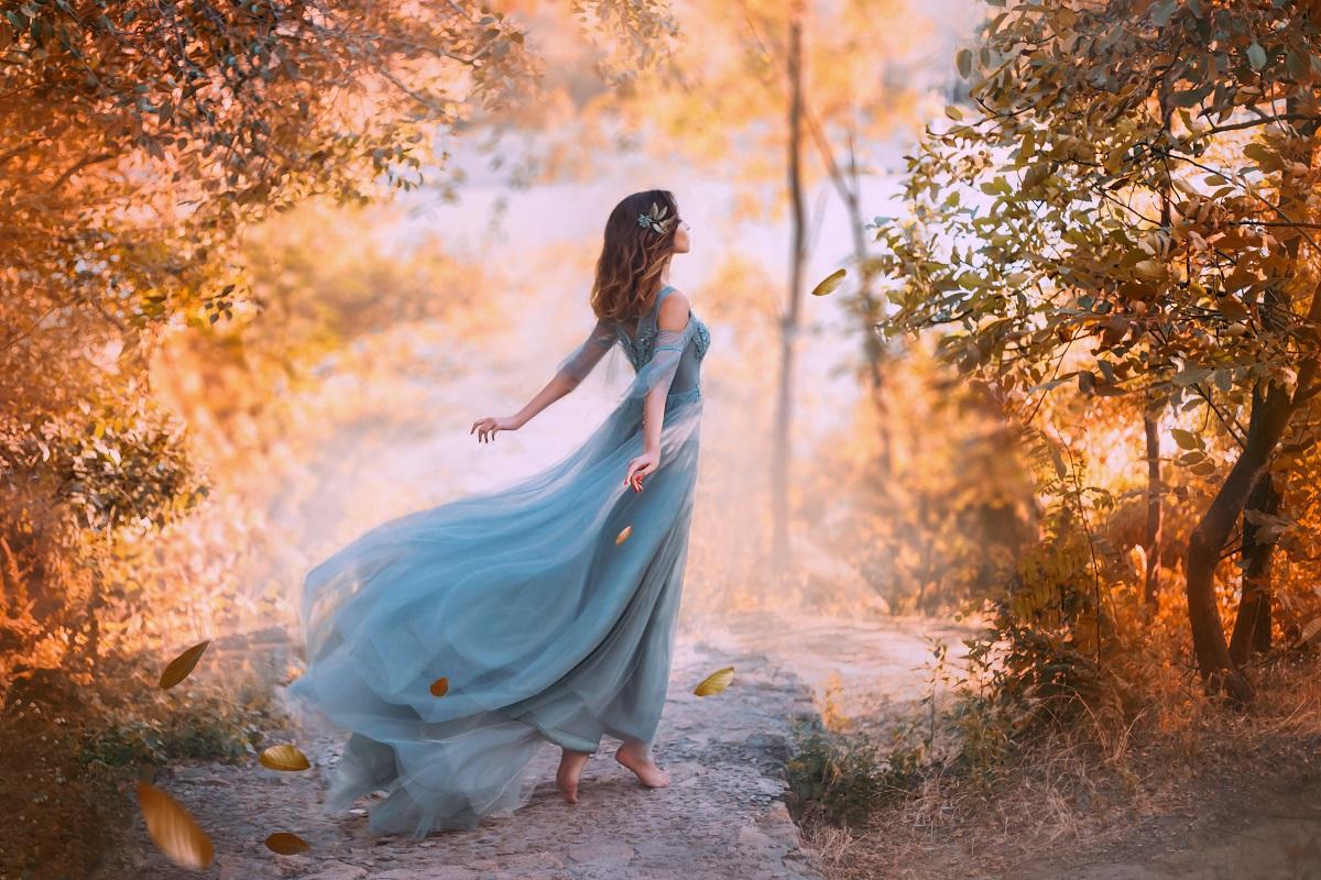 O femeie frumoasă care poartă o rochie albastră și privește în zare într-o pădure arămie de toamnă, fiind una din acele zodii care se fac remarcate toamna aceasta