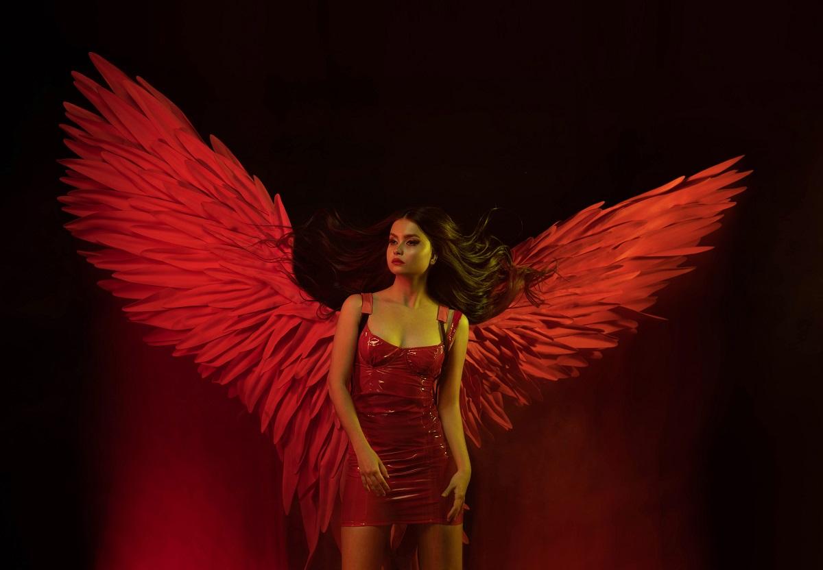 O femeie frumoasă îmbrăcată într-o rochie roșie care are în spate o pereche de aripi mari, roșii și reprezintă una din acele zodii extrem de geloase