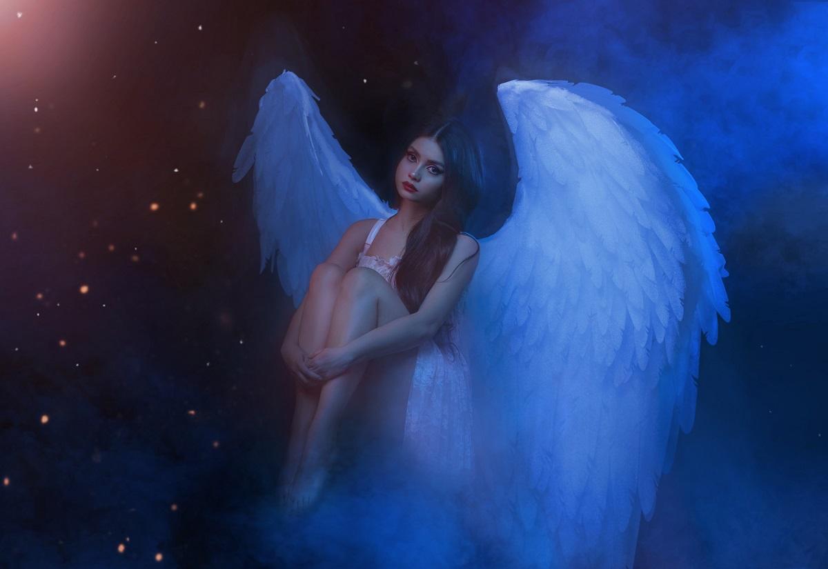 O femeie frumoasă care poartă o rochie albă și aripi de înger în timp ce își ține genunchii între brațe și privește tristă fiind una din acele zodii ghinioniste în ziua de 29 septembrie 2021