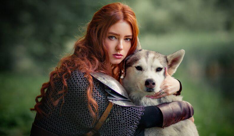 O femeie frumoasă cu părul roșcat care ține în brațe cu caine în timp ce portretizează acele zodii îndrăznețe