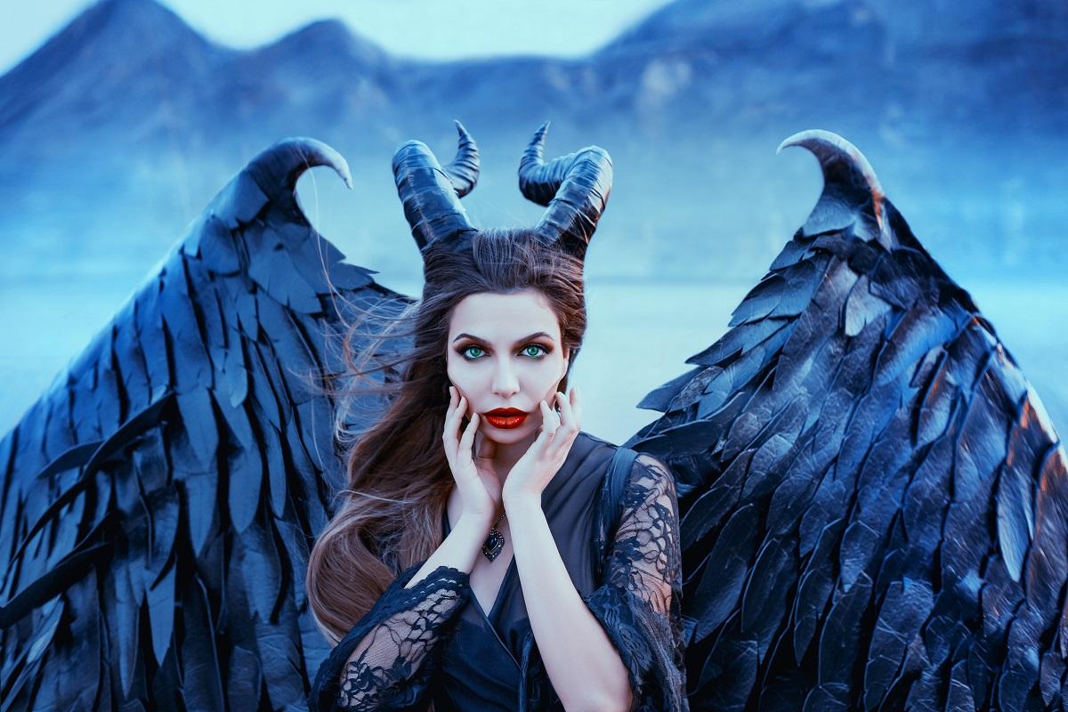 O femeie frumoasă care poartă aripi negre și o pereche de coarne în timp ce se mângâie pe față pentru a ilustra una din acele zodii invidioase