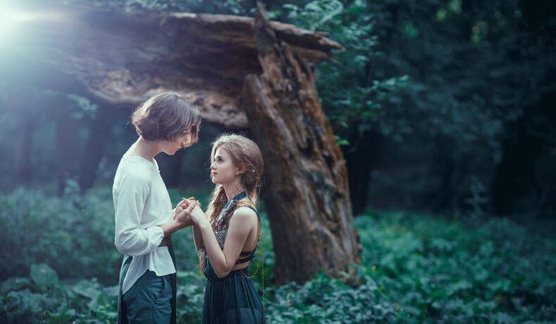 Un cuplu de îndrăgostiți într-o pădure în timp ce se țin de mâini și se privesc în ochi fiind zodii iubitoare