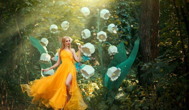 O femeie frumoasă care poartă o rochie galbenă și se află într-o pădure printre flori albe în timp ce portretizează una din acele zodii noroacoase în ziua de 1 octombrie 2021