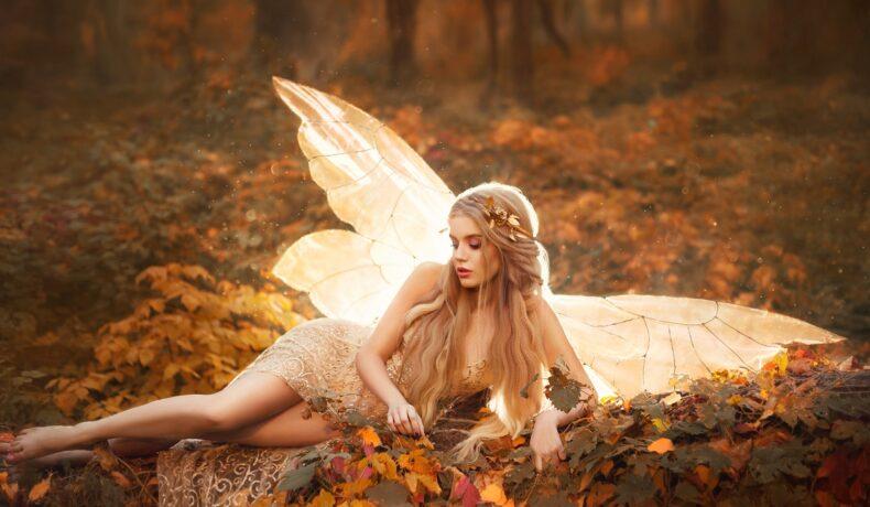 O femeie frumoasă, zână, care poartă o rochie aurie și stăpe un covor de frunze aurii într-o pădure pe timp de toamnă