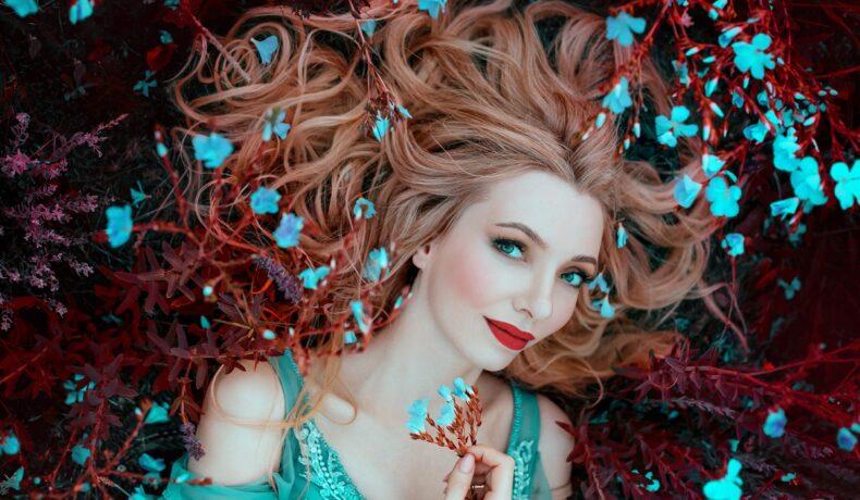 O femeie frumoasă care poartă o rochie albastră și stă întinsă e un pat de frunze maro în timpce în părul său se află flori albastre care simbolizează acele zodii norocoase în ziua de 24 septembrie 2021