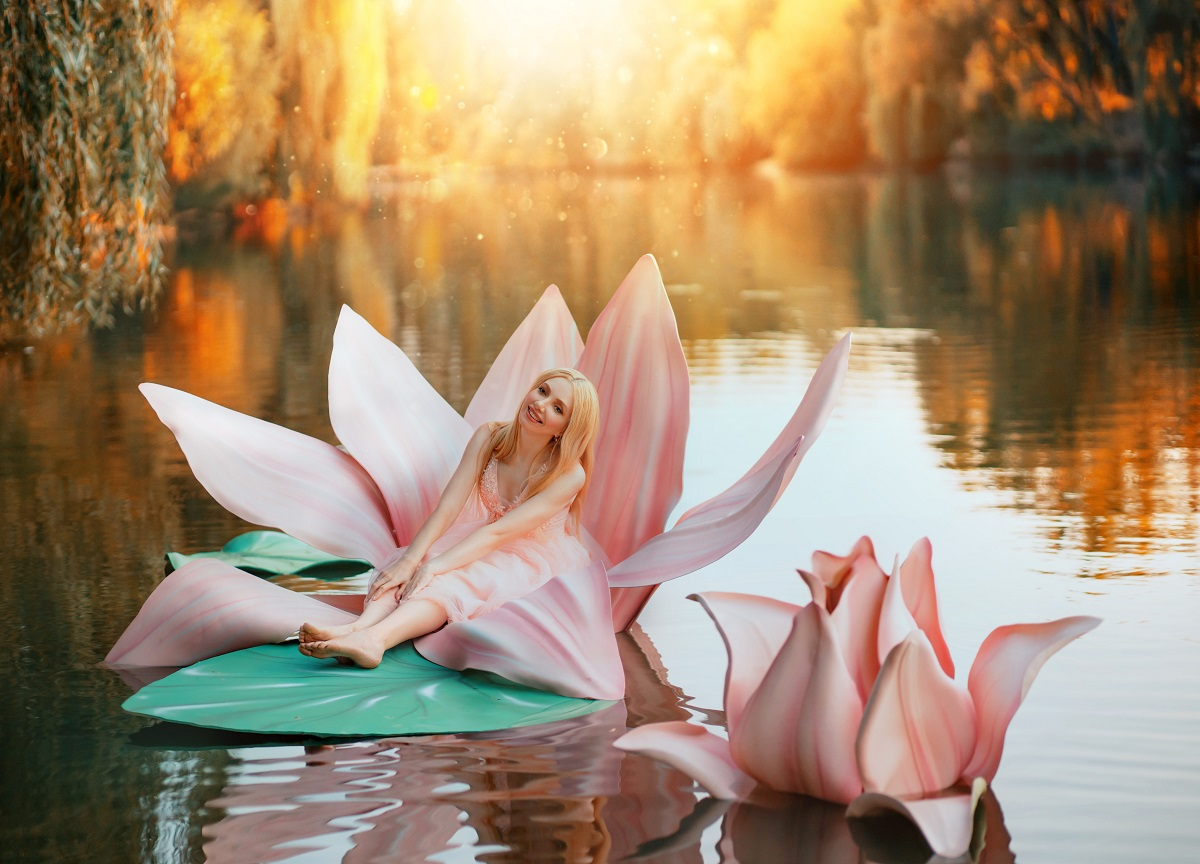 O femeie frumoasă care poartă o rochie roz și stă pe o floare de nufăr în mijlocul unui lac în timp ce reprezintă una din acele zodii norocoase în ziua de 29 septembrie 2021