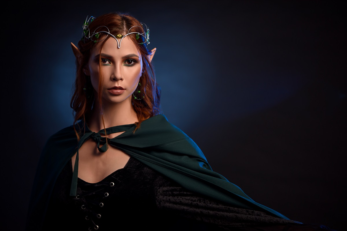 O femeie frumoasă elf care paortă o mantie verde și o coroniță pe cap reprezentând una din acele zodii extrem de puternice