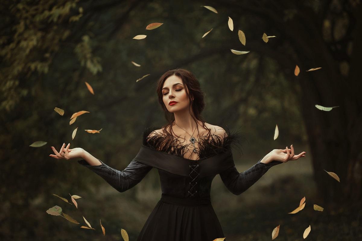O femeie frumoasă îmbrăcată într-o rochie neagră în timp ce se află într-o pădure iar în jurul său plutesc în cerc frunzele copacilor pentru a potrtretiza una din acele zodii răzbunătoare