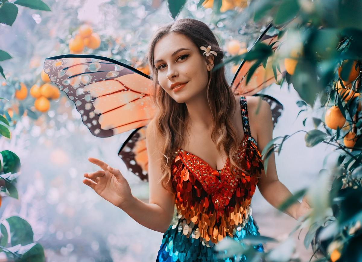 O femeie frumoasă cu aripi de fluture care poartă un top portocaliu și o fustă albastră în timp ce face cu mâna printre flori pentru a reprezenta una din acele zodii vorbărețe